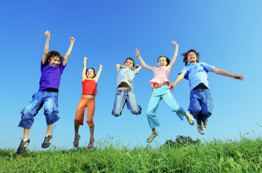 Group of five happy children jumping on meadow.
